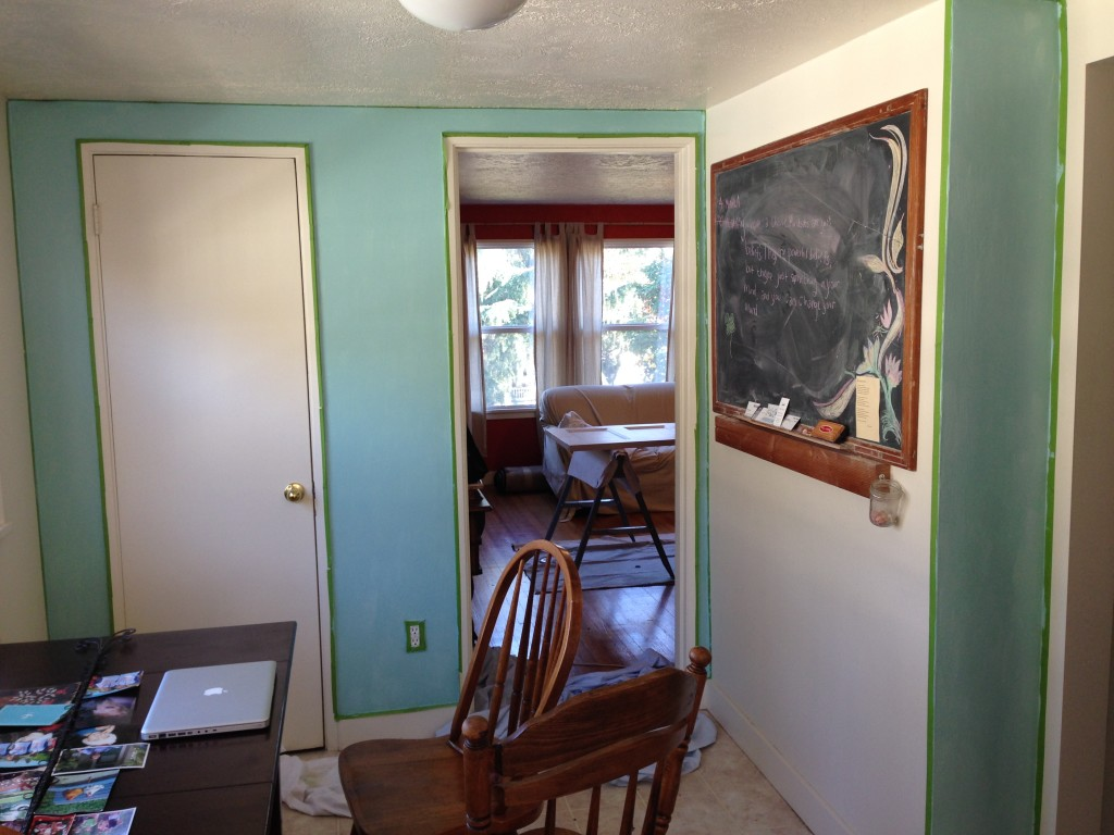 """The first coat of blue! I know it looks like we missed the side where the chalkboard was, but we were going for what they call an """"accent wall."""" That basically means painting a bright color but not over the whole room."""